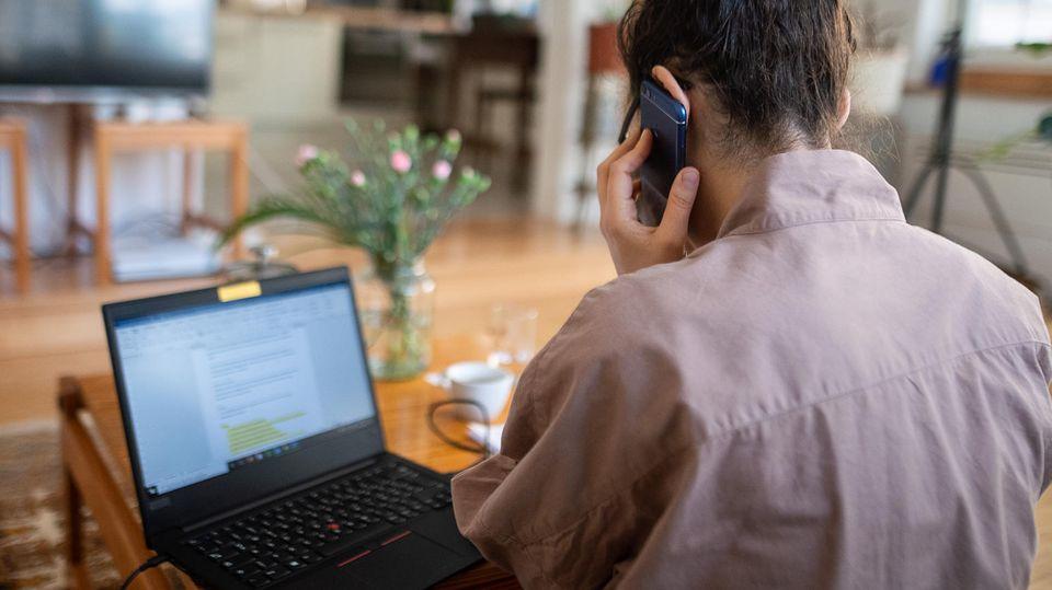 Eine Frau nimmt aufgrund der Ausbreitung des Coronaviruses aus ihrem Wohnzimmer an einer Telefonkonferenz teil.