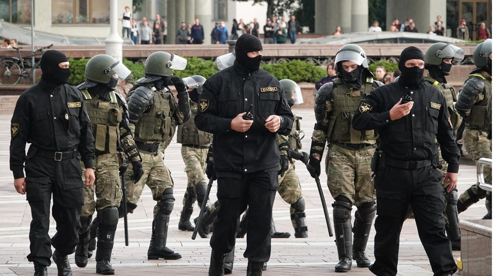 Polizisten in grüner oder schwarzer Kampfmontur - manche mit Sturmhauben - gehen in einer ungeordneten Gruppe über einen Platz