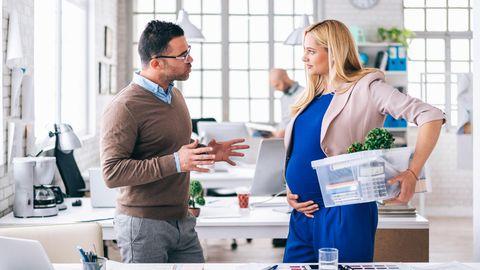 Eine schwangere Frau im Gespräch mit ihrem Chef