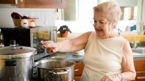 Eine alte Frau steht am Herd und kocht