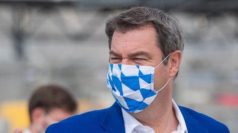 Bayerns Ministerpräsident Markus Söder trägt zum blauen Jackett einen Mund-Nasen-Schutz in weiß-blau