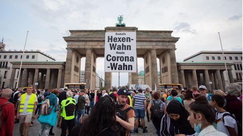 """Vor dem Brandenburger Tor in Berlin steht eine Menschenmenge. Jemand hält ein Schild """"Damals Hexenwahn, heute Coronawahn"""" hoch"""