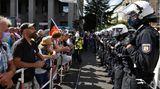 Berlin, Deutschland. Eine Polizeikette steht an Absperrgittern Demonstranten gegenüber. Tausende Menschen versammeln sich in der Hauptstadt, um gegen die Corona-Politik zu protestieren. Weil sie sich trotz mehrfacher Aufforderung nicht an die Abstandsregeln halten, löst die Polizei die Kundgebung am frühen Nachmittag auf.