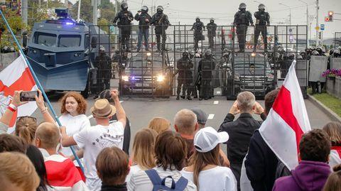 Demonstranten und Bereitschaftspolizisten stehen sichauf einer Straße in Minsk gegenüber