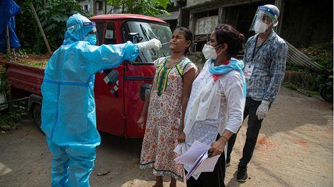 Ein Mitarbeiter des indischen Gesundheitswesens nimmt von einer Anwohnerin einen Abstrich für einen Coronatest