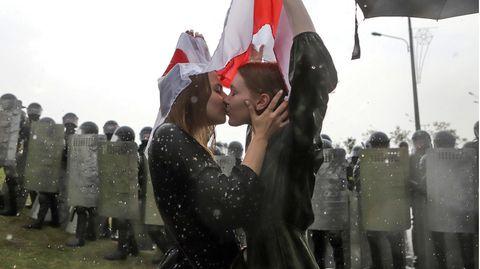 Belarus, Minsk: Zwei Demonstrantinnen küssen sich vor einer Riege von Bereitschaftspolizisten, bedeckt von einer ehemaligen belarussischen Nationalflagge während einer Protestkundgebung gegen Alexander Lukaschenko