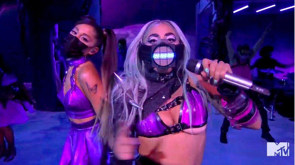 Eine blonde und eine brünette Frau tanzen mit Atemmasken und knappen Outfits auf einer blau beleuchteten Bühne