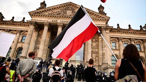 Teilnehmer der BerlinerKundgebung gegen die Corona-Maßnahmen stehen vor dem Reichstag, ein Teilnehmer hält eine Reichsflagge mit schwarz-weiß-roten Querstreifen.
