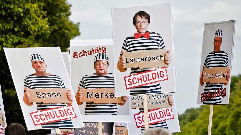 Plakate mit Fotomontagen und Bildern von Politikern und Journalisten
