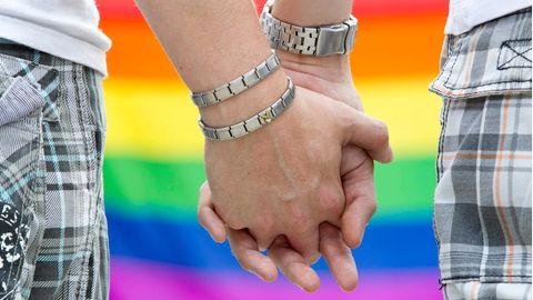 Die Hände zweier Männer, ineinander verschränkt, vor Regenbogenfahne