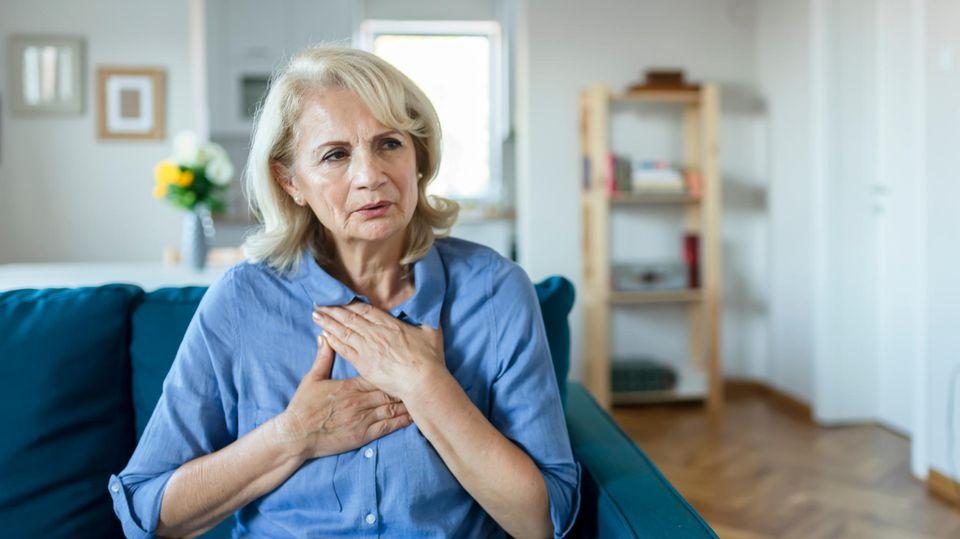 Eine ältere Frau hält sich die Brust