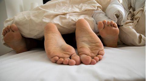 Eine junge Frau und ein junger Mann liegen gemeinsam in einem Bett (gestellte Szene)