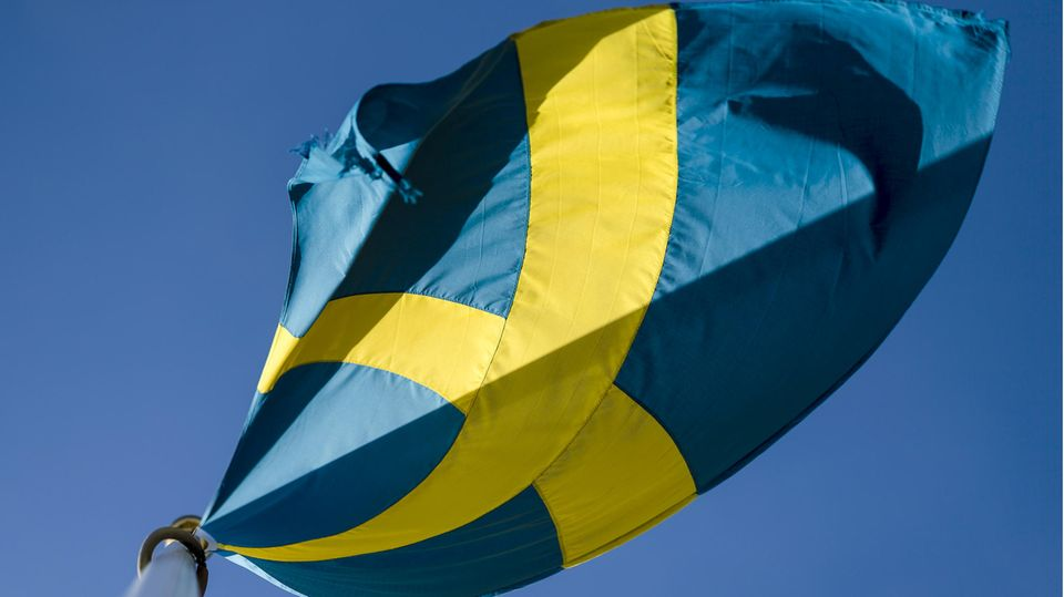 Die schwedische Flagge weht vor blauem Himmel im Wind