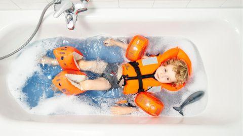 Ein Kind mit Schwimmflügeln in der Badewanne