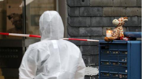Eine Person in weißem Overall geht auf einen Hauseingang zu. Rechts von ihr sind blaue Briefkästen, auf denen eine Kerze brennt