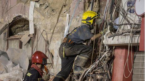 Zwei Retter - einer mit rotem, einer mit gelbem Helm - klettern in den Trümmern eines eingestürzten Gebäudes