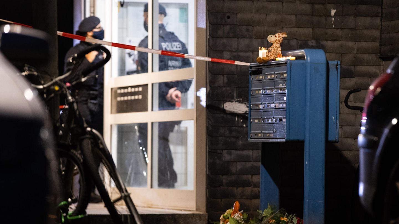 Polizisten stehen im Eingang eines Wohnhauses