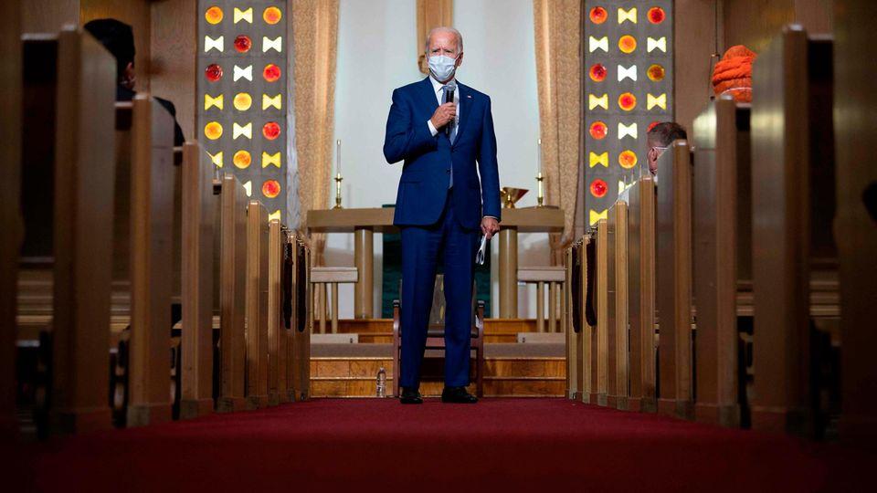 Ein weißhaariger Mann mit Atemmaske und blauem Anzug spricht im Mittelgang einer Kirche in ein Mikro