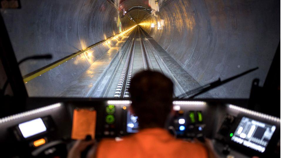 Bild 1 von 9der Fotostrecke zum Klicken:Der längste Eisenbahntunnel der Welt  Das ist der 2016 eröffnete Gotthard Basistunnelmit einer Länge von 57 Kilometern. Autos und Lastwagen werden auf die Schiene gebracht. Personenzüge rauschen teils mit 200 Kilometern in der Stunde hindurch, die Fahrt dauert keine 20 Minuten.