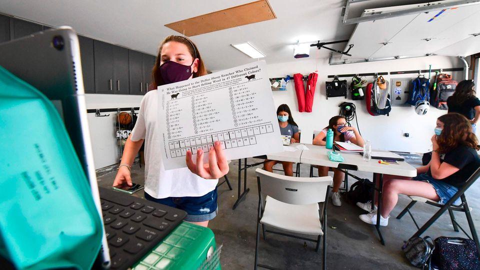 Siebtklässlerin Mia Friedlander geht in einer Garage in Kalifornien am Laptop mit ihrem Lehrer die Mathe-Aufgaben durch