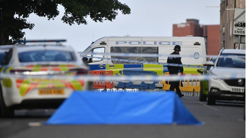 Ein Polizeibeamter und Fahrzeuge der Polizei stehen an einer Absperrung in der Irving Street in Birmingham