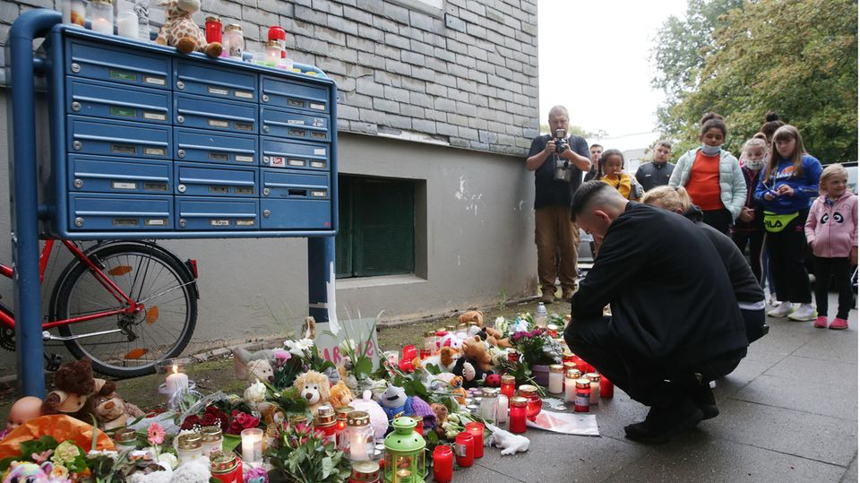 Solingen: Trauende knien vor Blumen, Kerzen und Stofftieren vor dem Haus, wo fünf tote Kinder entdeckt worden waren