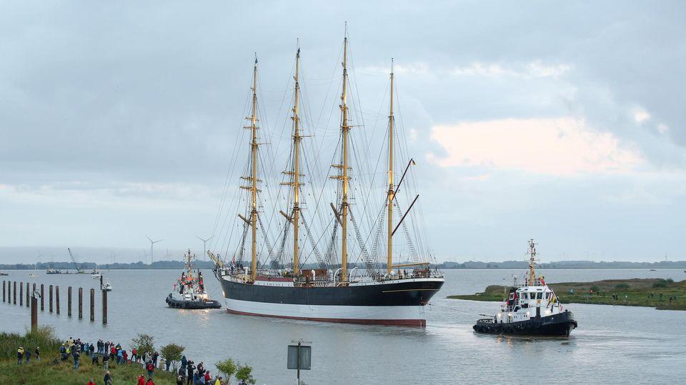 Ein altes Segelschiff mit vier Masten hat am Bug und am Heck jeweils einen Schlepper, während es auf der Elbe fährt.