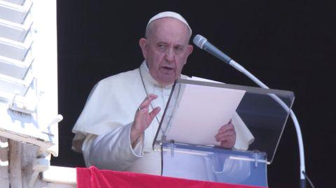 Der Papst steht in weißem Gewand an einem Fenster und spricht in ein Mikrofon. Vor ihm liegen Zettel auf einem Plexiglas-Pult