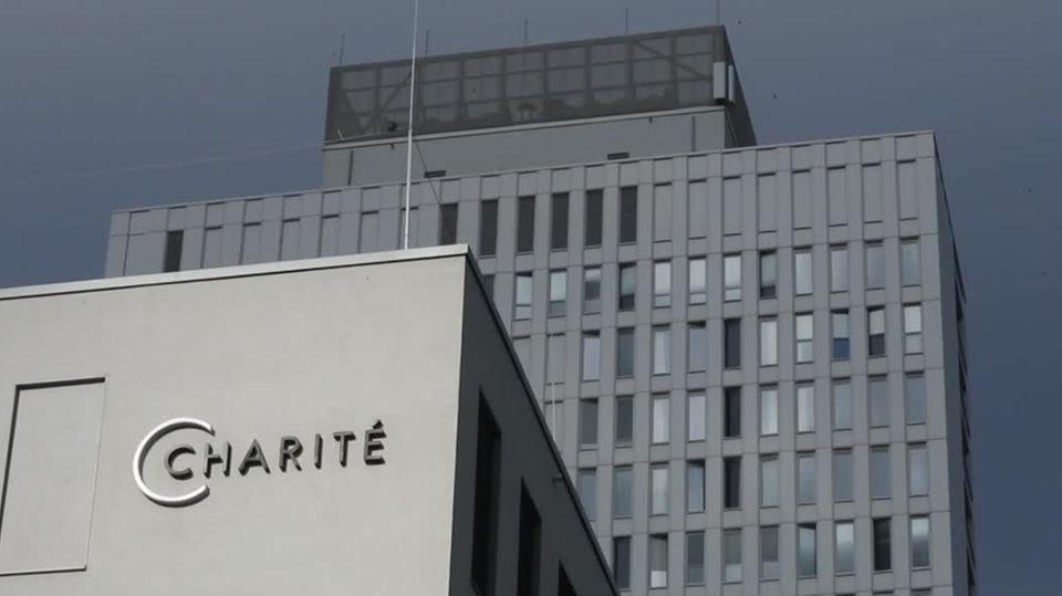 """Zwei graue Hochhäuser stehen vor dem Himmel über Berlin. Am vorderen ist der metallene Schriftzug """"Charité"""" angebracht"""