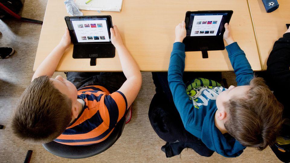 Schüler einer 5. Klasse lernen mit iPads im Englischunterricht
