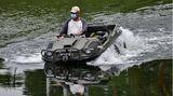 Santa Cruz de Yojoa, Honduras. Ein Mann mit Schutzmaske fährt in einem Amphibien-Fahrzeug über den größten See des Landes. Viele Hodnduraner suchten während der Pandemie Schutz in den Bergen oder an touristischen Plätzen wie dem Lake Yojoa.