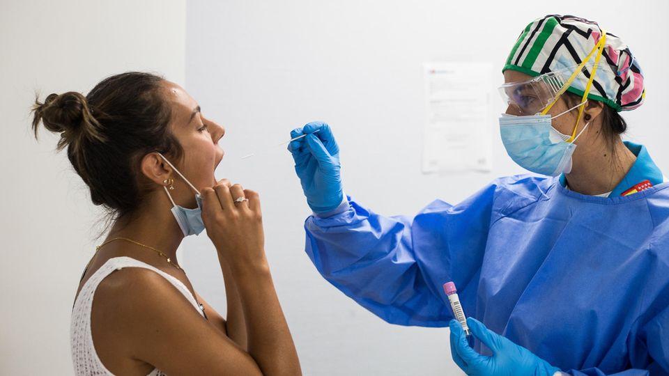 Einemedizinische Mitarbeiterin nimmt in einem  Covid-19-Testzentrum in Madrid einen Abstrich bei einer Patientin