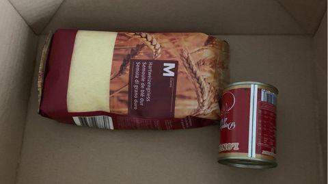 Ein Pfund Hartweizengrieß und eine Dose Tomatenmark liegen in einem Karton