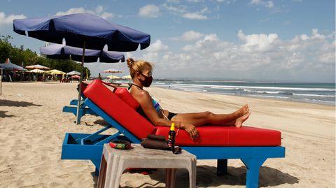Eine Frau liegt im Bikini und mit Mund-Nasen-Schutz auf einer Liege mit rotem Polster am Strand