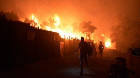 Migranten rennen während ein Feuer im Flüchtlingslager Moria auf der Insel Lesbos brennt. Medienberichten zufolge stehen auch Wohncontainer in Flammen, weshalb die Behörden das Lager evakuierten.