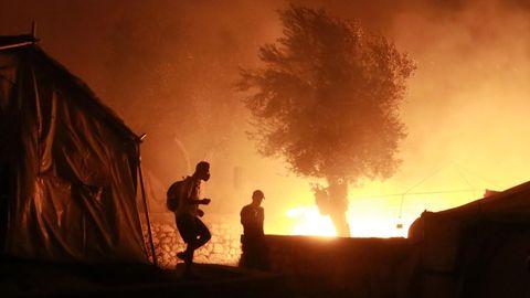 Feuer ist im Flüchtlingslager Lesbos zu sehen, vorn gehen zwei Personen