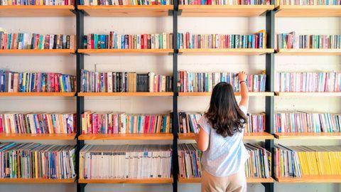 Frau vor einem Regal mit Schulbüchern