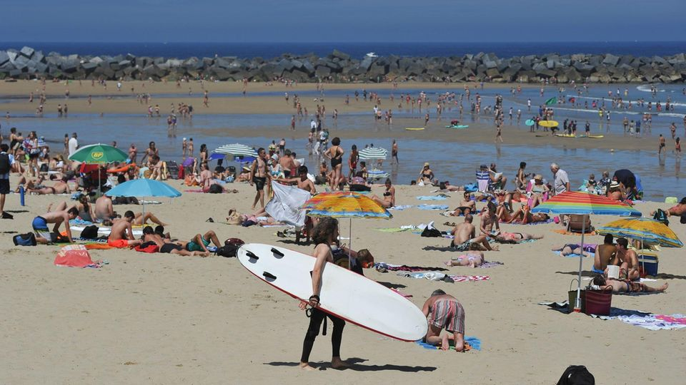 Der gefüllte Strand mit einer Surferin