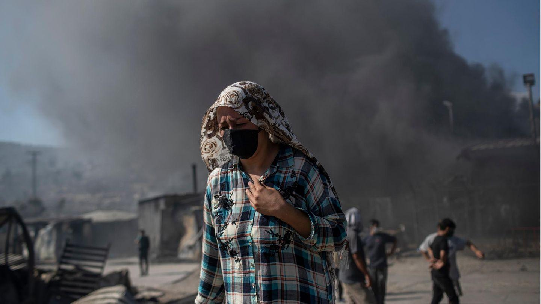 Eine Frau mit Mund- und Kopfbedeckung im zerstörten Flüchtlingslager Moria auf Lesbos