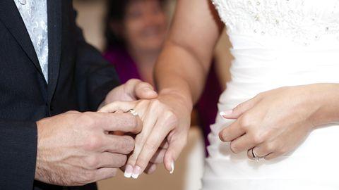 Bräutigam steckt Braut den Hochzeitsring an