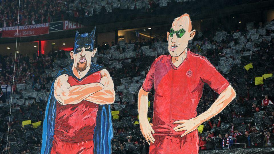 Karikaturen im Stadion: Franck Ribery als Batman und Arjen Robben als Robin