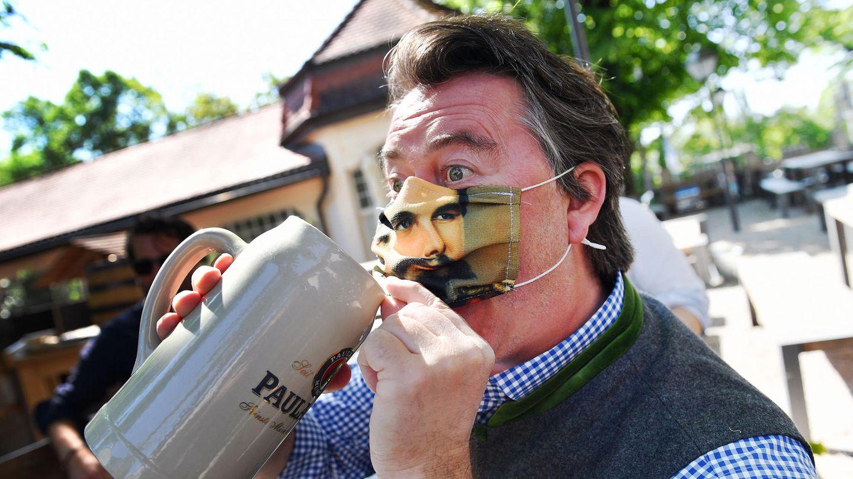 Ein Mann trinkt Bier im Paulaner-Biergarten