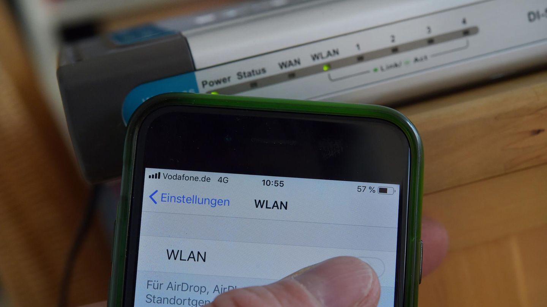 Wlan-Signal verstärken: Smartphone-Nutzer vor Wlan-Router
