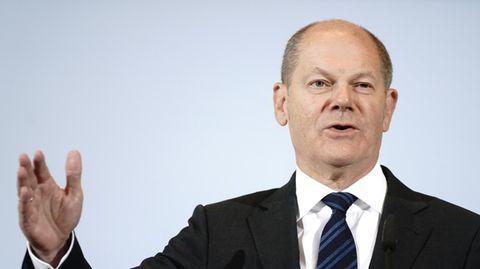 """Ein Mann mit kurzem Haarkranz steht in Anzug und Krawatte vor einer blauen Wand mit """"Bundesministerium der Finanzen""""-Schriftzug"""