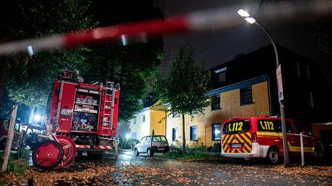 Feuerwehrfahrzeuge stehen am späten Abend an einem Haus hinter einer Absperrung