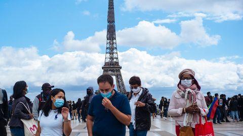 Passanten tragen am Platz Trocadero in der Nähe des Eiffelturms Mundschutze und Gesichtsmasken.