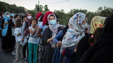 Frauen stehen an, um Essen zu erhalten, in der Nähe des ausgebrannten Flüchtlingslagers Moria