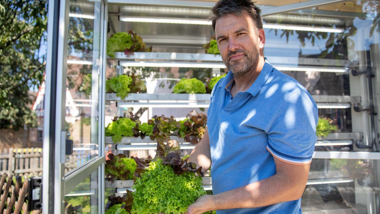 Gärtnermeister Jochen Haubner steht mit einem Salat vor dem Salatautomaten in Nürnberg