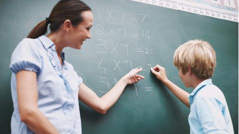 Mathematiklehrerin und Schüler an der Tafel