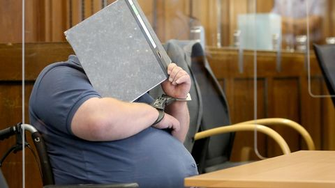 Einer von zwei Angeklagten wird von Justizbeamten mit dem Rollstuhl in den Gerichtssaal gefahren
